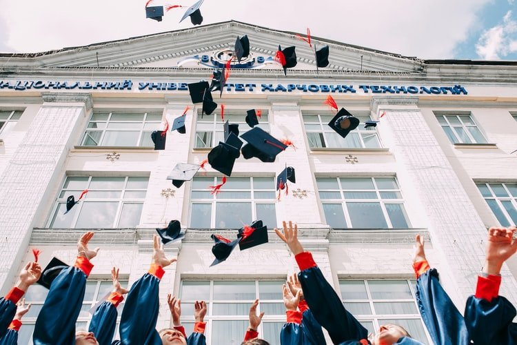 Students throwing their mortar boards in the air